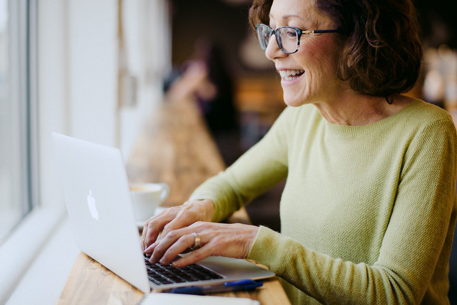smiling woman looking at laptop in coffee shop