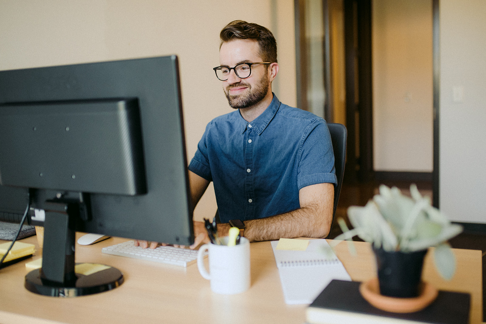 man sitting at office desk looking at desktop computer