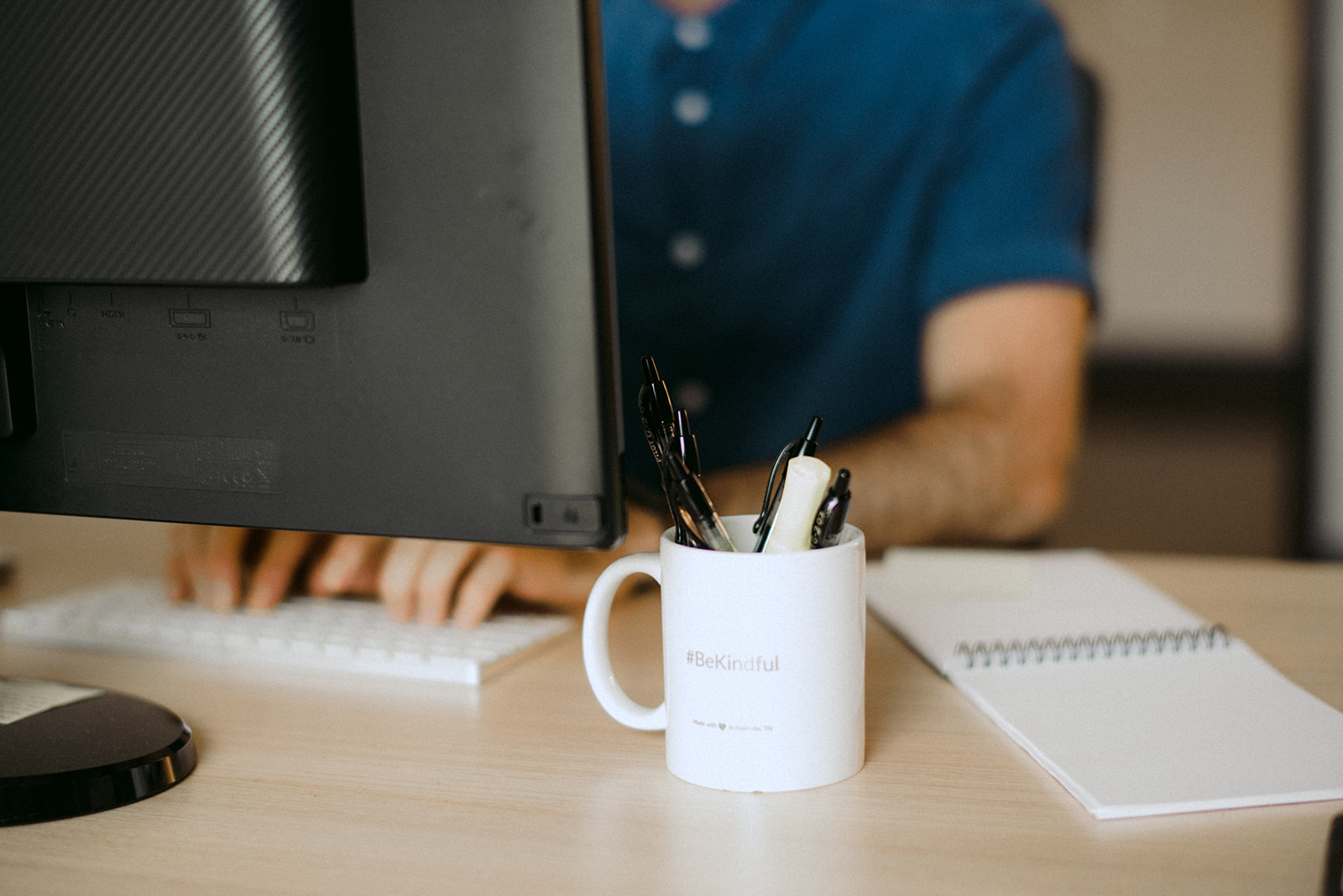 man working on computer with be kindful mug in foreground