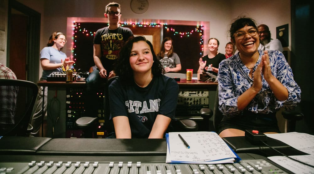 Young girl smiling in an audio recording studio with teacher clapping beside her