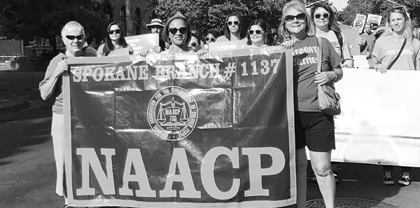 Grayscale image showing protestors with banner that says Spokane Branch 1137 NAACP