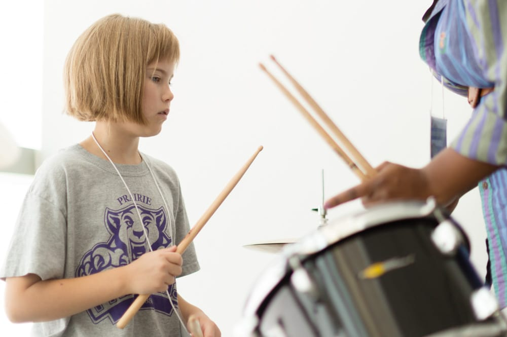 Teacher showing young girl how to play drums at Omaha Girls Rock