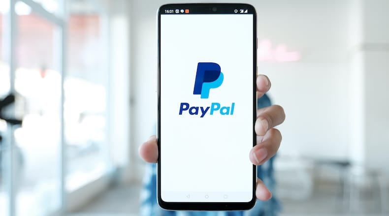 PayPal for nonprofits header image showing person holding iPhone with PayPal logo