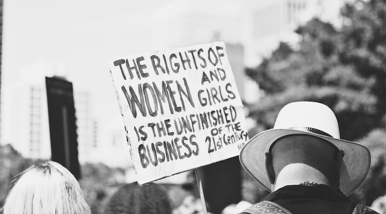 Black and white photograph showing protest and sign that says The Rights Of Women And Girls Is The Unfinished Business of the Twenty First Century